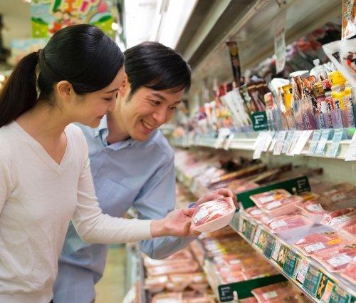 スーパーで購入するお肉を吟味している夫婦